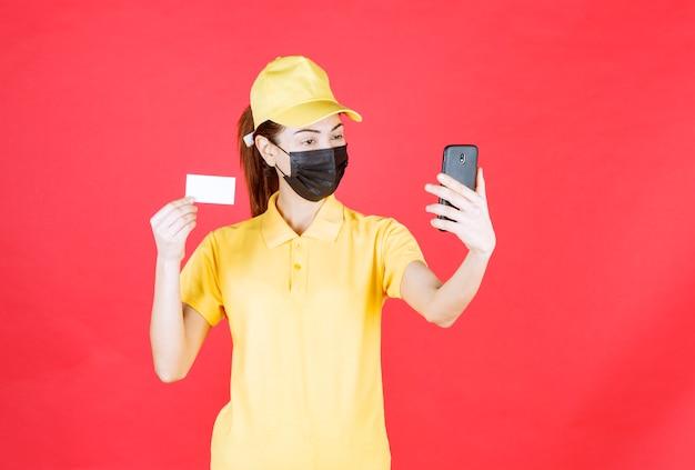 Vrouwelijke koerier in geel uniform en zwart masker die een smartphone vasthoudt en haar selfie neemt terwijl ze haar visitekaartje presenteert