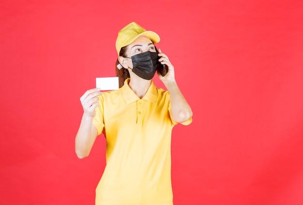 Vrouwelijke koerier in geel uniform en zwart masker die een smartphone vasthoudt en haar visitekaartje presenteert terwijl ze met de telefoon praat