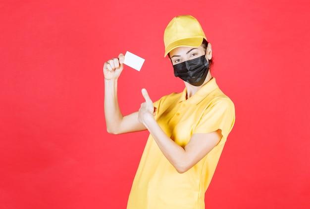 Vrouwelijke koerier in geel uniform en zwart masker die haar visitekaartje presenteert en duim toont