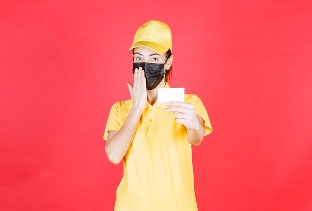 Vrouwelijke koerier in geel uniform en zwart masker die haar visitekaartje presenteert en er attent en verward uitziet