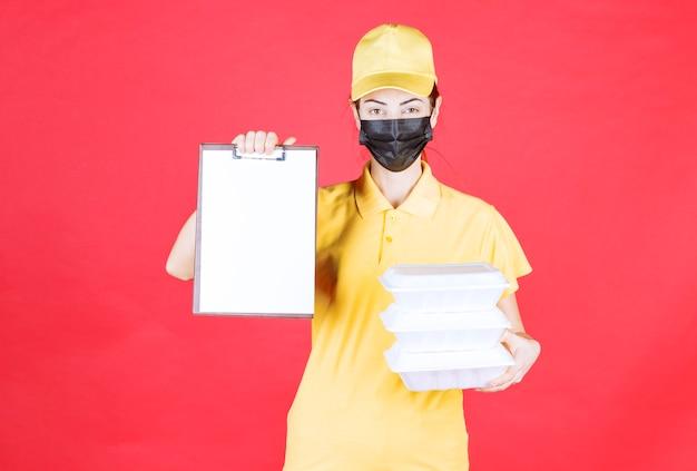 Vrouwelijke koerier in geel uniform en zwart masker die meerdere afhaalpakketten vasthoudt en de handtekeninglijst presenteert
