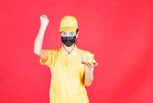 Vrouwelijke koerier in geel uniform en zwart masker levert een noedelbeker af en toont haar vuist