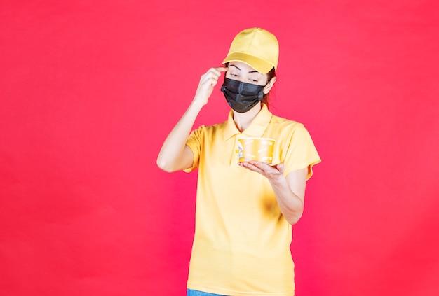 Vrouwelijke koerier in geel uniform en zwart masker levert een noedelbeker af en ziet er verward en attent uit
