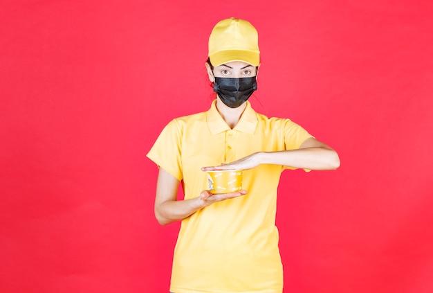 Vrouwelijke koerier in geel uniform en zwart masker levert een noedelbeker af