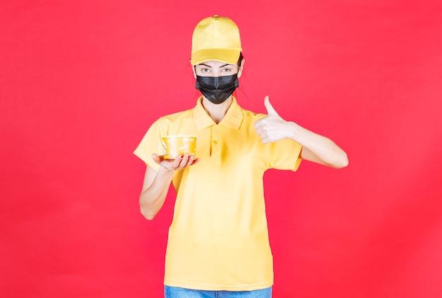 Vrouwelijke koerier in geel uniform en zwart masker levert een noedelbeker en toont een handteken voor plezier