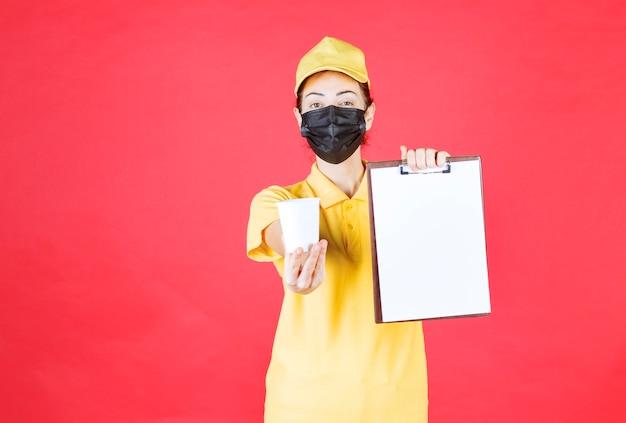 Vrouwelijke koerier in geel uniform en zwart masker met een afhaalbeker en een klantenlijst
