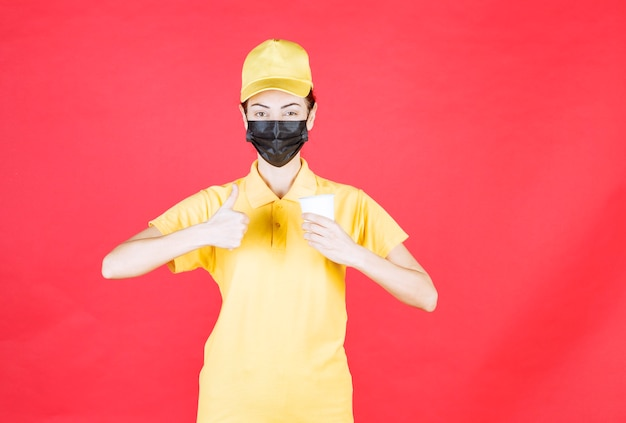 Vrouwelijke koerier in geel uniform en zwart masker met een afhaalbeker en genietend van de smaak