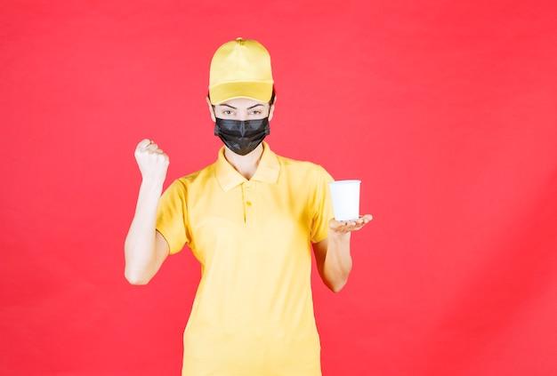 Vrouwelijke koerier in geel uniform en zwart masker met een afhaalbeker en haar vuist tonend