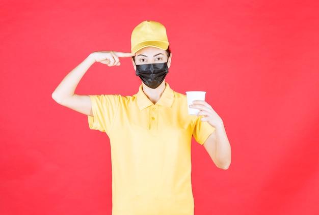 Vrouwelijke koerier in geel uniform en zwart masker met een afhaalbeker en ziet er verward en attent uit