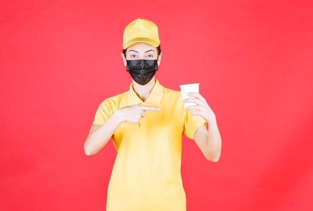 Vrouwelijke koerier in geel uniform en zwart masker met een afhaalbeker