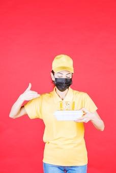 Vrouwelijke koerier in geel uniform en zwart masker met een afhaalpakket en ruikend aan het product