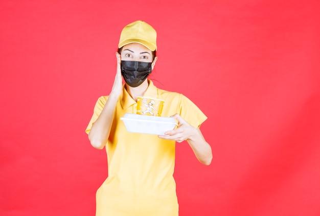 Vrouwelijke koerier in geel uniform en zwart masker met een afhaalpakket en ziet er verward en attent uit
