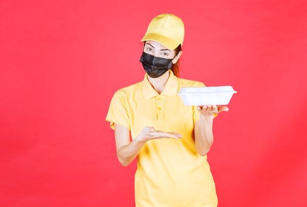 Vrouwelijke koerier in geel uniform en zwart masker met een afhaalpakket
