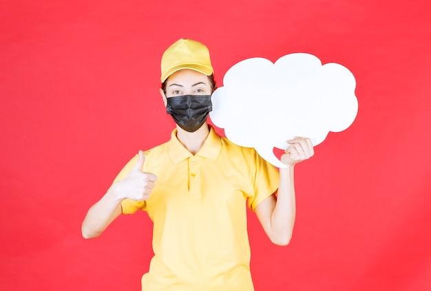 Vrouwelijke koerier in geel uniform en zwart masker met een infobord in de vorm van een wolk en een teken van plezier