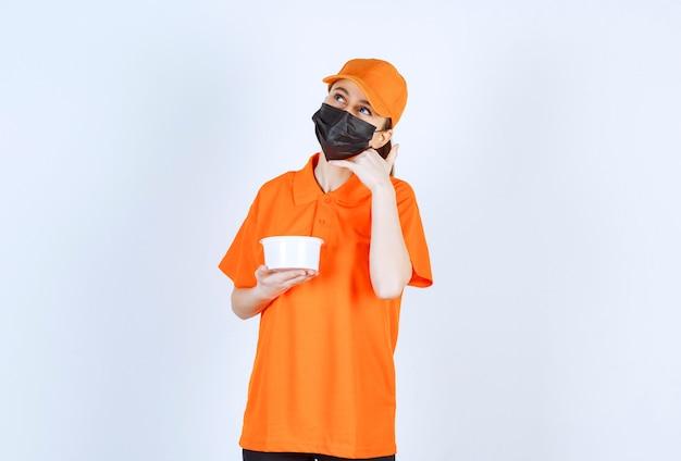 Vrouwelijke koerier in geel uniform en zwart masker met een plastic beker en om te bellen