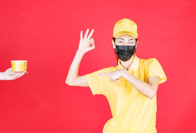 Vrouwelijke koerier in geel uniform en zwart masker ontvangt een noedelbeker voor bezorging en toont een positief handteken