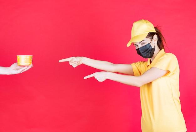 Vrouwelijke koerier in geel uniform en zwart masker ontvangt een noedelbeker voor bezorging en verlangt ernaar om haar armen te nemen