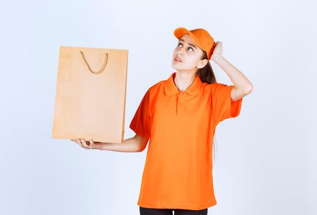 Vrouwelijke koerier in geel uniform levert een boodschappentas en ziet er attent uit