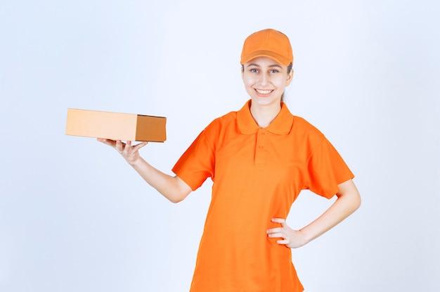 Vrouwelijke koerier in geel uniform levert een kartonnen doos.