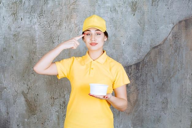 Vrouwelijke koerier in geel uniform met een afhaalbeker, denkend en een goed idee hebbend