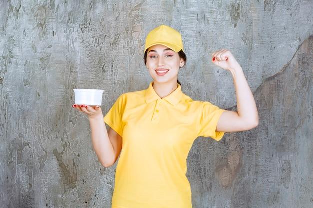 Vrouwelijke koerier in geel uniform met een afhaalbeker en geniet van het product