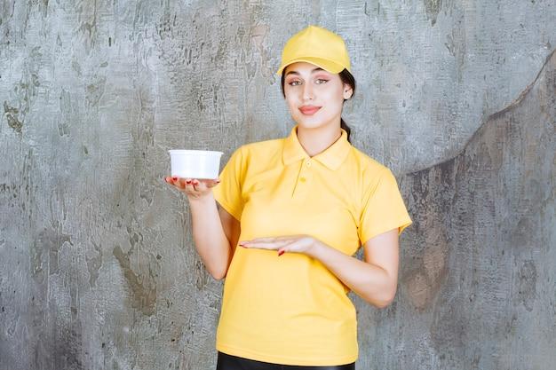 Vrouwelijke koerier in geel uniform met een afhaalbeker.