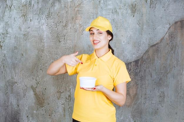 Vrouwelijke koerier in geel uniform met een afhaalbeker