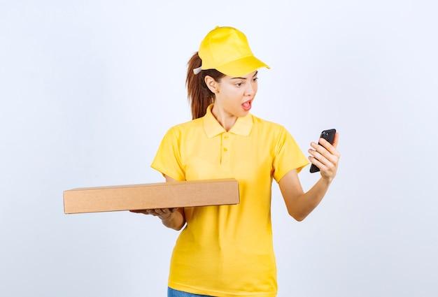 Vrouwelijke koerier in geel uniform met een kartonnen pakket terwijl ze haar telefoon controleert en glimlacht.
