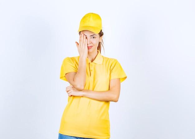 Vrouwelijke koerier in geel uniform sluitend deel van haar gezicht en oog.