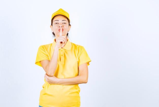 Vrouwelijke koerier in geel uniform vraagt om stilte.