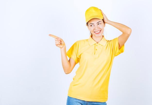 Vrouwelijke koerier in geel uniform wijzend naar ergens.