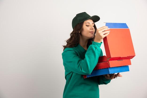 Vrouwelijke koerier in groen uniform die de hete pizza ruikt.
