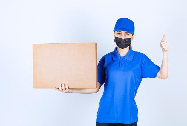 Vrouwelijke koerier in masker en blauw uniform die een groot kartonnen pakket houdt en positief handteken toont.