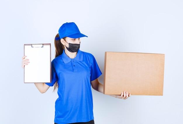Vrouwelijke koerier in masker en blauw uniform die een groot kartonnen pakket vasthoudt en de checklist voor ondertekening presenteert