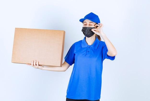 Vrouwelijke koerier in masker en blauw uniform die een groot kartonnen pakket vasthoudt en een positief handteken toont