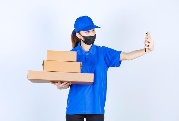 Vrouwelijke koerier in masker en blauw uniform die een voorraad kartonnen dozen vasthoudt en een videogesprek voert of haar selfie neemt