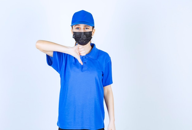 Vrouwelijke koerier in masker en blauw uniform met duim omlaag teken