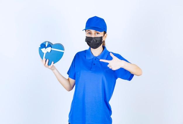 Vrouwelijke koerier in masker en blauw uniform met een geschenkdoos in de vorm van een hart