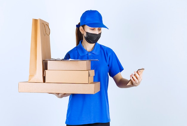 Vrouwelijke koerier in masker en blauw uniform met een kartonnen boodschappentas en meerdere dozen terwijl ze haar selfie neemt.