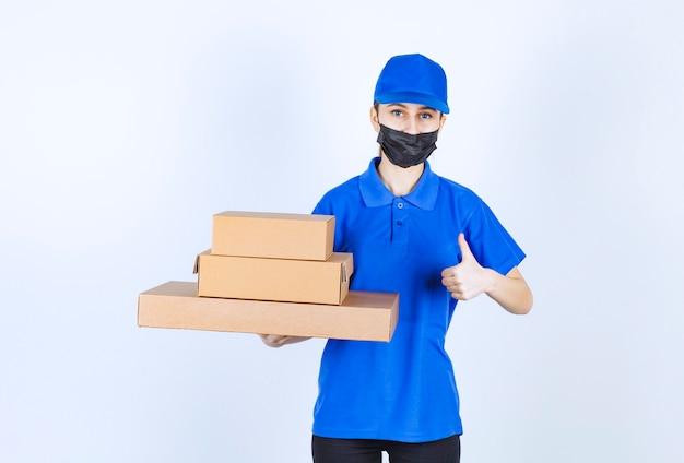 Vrouwelijke koerier in masker en blauw uniform met een voorraad kartonnen dozen en een positief handteken