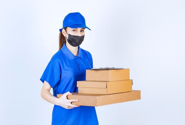 Vrouwelijke koerier in masker en blauw uniform met een voorraad kartonnen dozen