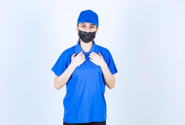 Vrouwelijke koerier in masker en blauw uniform wijzend op zichzelf.