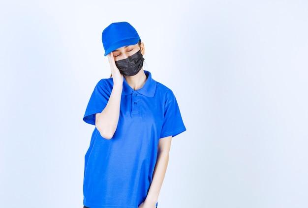 Vrouwelijke koerier in masker en blauw uniform ziet er slaperig en moe uit.
