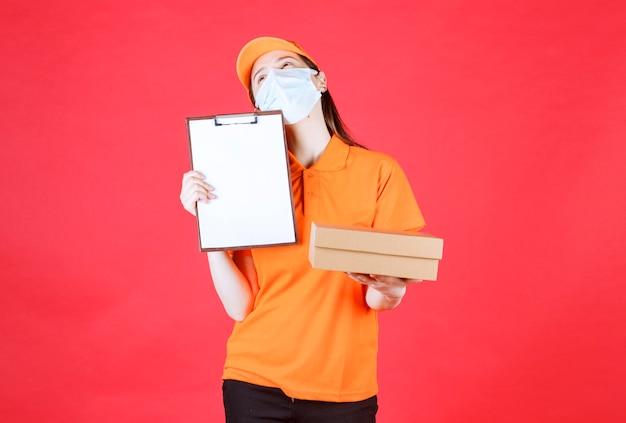 Vrouwelijke koerier in oranje kleur dresscode en masker die een kartonnen doos vasthoudt en de lijst ter ondertekening presenteert terwijl ze nadenkt.