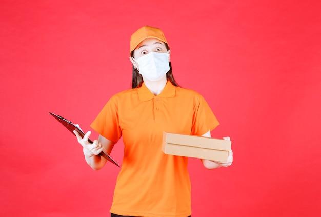 Vrouwelijke koerier in oranje kleur dresscode en masker met een kartonnen doos en de lijst voor ondertekening.