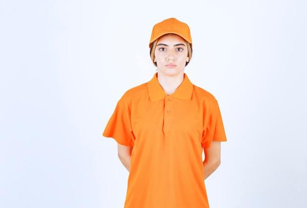 Vrouwelijke koerier in oranje uniform blijft kalm en ontspannen