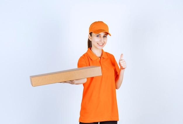 Vrouwelijke koerier in oranje uniform die een afhaalpizzadoos vasthoudt en een positief handteken toont