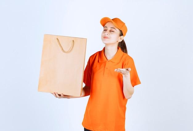 Vrouwelijke koerier in oranje uniform die een boodschappentas aflevert en het product erin ruikt