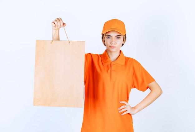 Vrouwelijke koerier in oranje uniform die een kartonnen boodschappentas aflevert en er attent uitziet