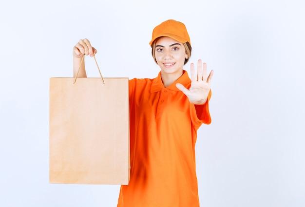 Vrouwelijke koerier in oranje uniform die een kartonnen boodschappentas aflevert en iemand tegenhoudt